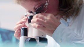 Handheld skott för låg vinkel av den mogna kvinnliga forskaren som ser till och med ett mikroskop stock video