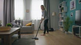 Handheld strzał młoda piękna dziewczyna vacuuming jej wygodnego mieszkanie zbiory