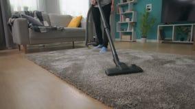 Handheld strzał młodej pięknej dziewczyny vacuuming dywan w jej wygodnym żywym pokoju zbiory wideo