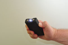 A handheld taser. A taser held in a mans hand on a white background stock photo