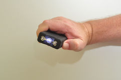 A handheld taser. A taser held in a mans hand on a white background royalty free stock photo
