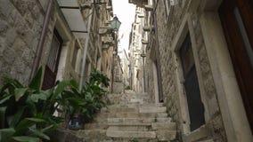 Handheld tracking shot a rustic narrow alleyway in Dubrovnik. Croatia stock footage