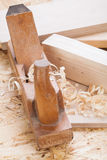Handheld wood plane with wood shavings. Close up view of a wooden handheld wood plane used to smooth and level the surface of a plank of wood surrounded with Royalty Free Stock Photography