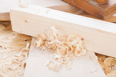 Handheld wood plane with wood shavings. Close up view of a wooden handheld wood plane used to smooth and level the surface of a plank of wood surrounded with Stock Image
