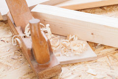 Handheld wood plane with wood shavings. Close up view of a wooden handheld wood plane used to smooth and level the surface of a plank of wood surrounded with Royalty Free Stock Image