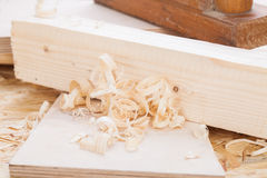 Handheld wood plane with wood shavings. Close up view of a wooden handheld wood plane used to smooth and level the surface of a plank of wood surrounded with Stock Photos