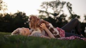 Handhelded-Gesamtlänge Blondine in zufälligem, ihren Hund beim Lügen streichelnd auf einem Plaid im Stadtpark auf dem Plaid stock footage