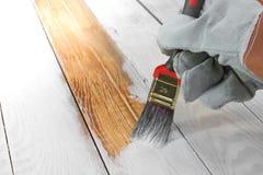 Handholding-Bürsten-malende weiße Farbe auf Holz lizenzfreie stockfotografie