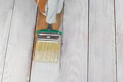 Handholding-Bürsten-malende weiße Farbe auf Holz stockbild