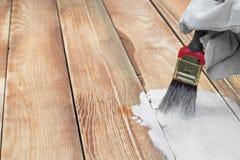 Handholding-Bürsten-malende weiße Farbe auf Holz lizenzfreie stockbilder