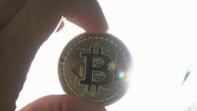 Handholding Bitcoin met Zonstralen die op Achtergrond gloeien stock footage
