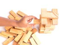 Handholding blockiert das hölzerne Spiel (jenga) lokalisiert auf weißem backgrou Lizenzfreie Stockfotografie