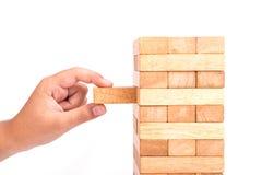 Handholding blockiert das hölzerne Spiel (jenga) lokalisiert auf weißem backgrou Stockfotografie