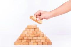 Handholding blockiert das hölzerne Spiel (jenga) lokalisiert auf weißem backgrou Lizenzfreies Stockbild