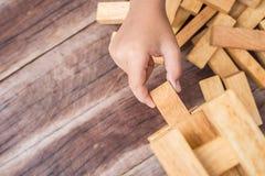 Handholding blockiert hölzernes Spiel (jenga) auf hölzernem Plankenhintergrund Lizenzfreie Stockfotos
