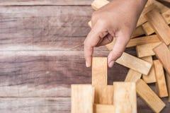 Handholding blockiert hölzernes Spiel (jenga) auf hölzernem Plankenhintergrund Stockfotos