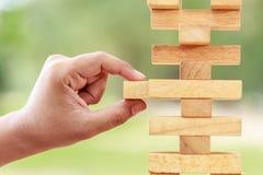 Handholding blockiert hölzernes Spiel (jenga) auf unscharfem grünem backgroun Lizenzfreie Stockbilder