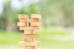 Handholding blockiert hölzernes Spiel (jenga) auf unscharfem grünem backgroun Lizenzfreie Stockfotos