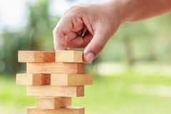 Handholding blockiert hölzernes Spiel (jenga) auf unscharfem grünem backgroun Lizenzfreies Stockfoto