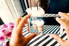 Handholding die mobiel en foto van bevroren koffie nemen stock foto