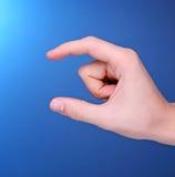 Handholding etwas klein in seinen Fingern Stockfoto