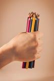 Handholding farbige Bleistifte lizenzfreie stockbilder