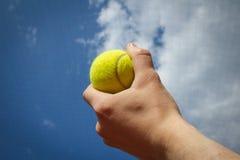 Handholding-Tenniskugel bis zum Himmel Lizenzfreie Stockbilder