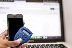 Handholdingtelefon- und -internet-Sicherheitsschlüssel und ATM-Karte mit Monitorvertretungsinternet-Geschäft als Hintergrund stockfoto