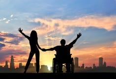 Handicapé dans le fauteuil roulant avec l'amie sur le fond de la ville Image stock