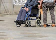 Handicapé dans un fauteuil roulant sur une rue de ville Image stock