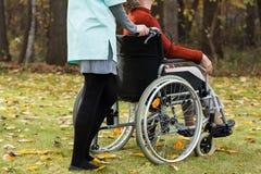 Handicapé et infirmière sur une promenade Photo stock