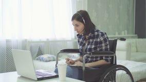 Handicapés de jeune femme, fauteuil roulant, travail à distance à la maison, casque d'ordinateur photo libre de droits