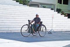Handicap. A maldivian man on a wheelchair outside a mosque at malè at maldives.august 2011 Stock Photo