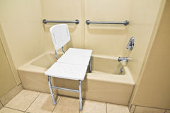 Handicap Bathing Chair. The chair helps the disabled and handicap use the bathtub easier with access at the height of a wheelchair. The wall handles help with Stock Photo