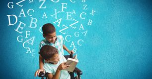 Handicap boy and brother reading book with alphabets flying over blue background Stock Photography