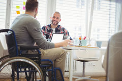 Handicap businessman discussing with colleague in office Stock Photography