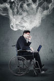 Handicap businessman expressing anger with smoke. Picture of handicap businessman sitting on a wheelchair and expressing anger with a laptop and smoke in his Stock Photography