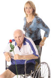 Handicap elderly man with younger woman. Isolated on white Stock Photos