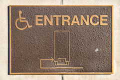 Handicap Entrance Sign. Made from rough textured metal on wall Stock Photos