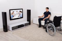 Handicap man watching television in living room Stock Photos