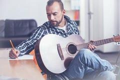 Handicap maturo vivace che scrive una canzone a casa fotografie stock libere da diritti