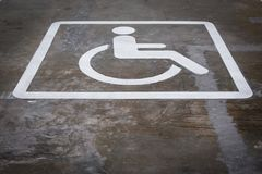 Handicap parking areas reserved for disabled people ,  White whe. Elchair icon on a gray asphalt parking lot Stock Images
