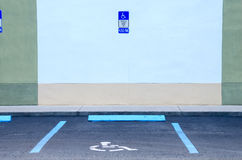 Handicap Parking Disabled Permit Spot. Handicapped parking disabled permit only spot with the handicapped logo painted on the parking spot, a sign on the wall Stock Images