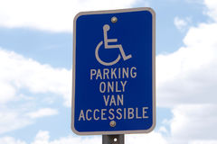 Handicap parking sign with sky background. Handicap parking sign against blue sky with white fluffy clouds in background Royalty Free Stock Photos