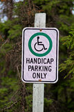 A handicap parking only sign with trees in the background.  Stock Photos