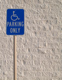 Handicap Parking Sign with White Textured Backgrou. Blue handicap parking sign with a white textured concrete block background that can be used for copy space Royalty Free Stock Photo
