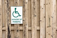 Handicap Parking sign on a wood slat fence Royalty Free Stock Photo