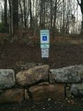 Handicap Parking Space. Handicapped parking space with stone wall and tree lined parking lot. Blue metal reflective motor vehicle warning sign Stock Photography