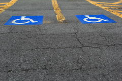 Handicap parking spots. Handicapped signs painted bright blue and white on concrete parking lot spaces Stock Image