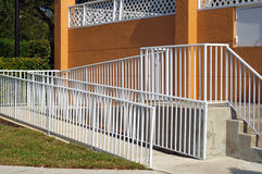 Handicap ramp with white railing and orange wall Royalty Free Stock Photo